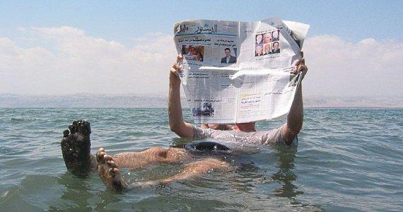 Люди плавают в Мёртвом море на поверхности